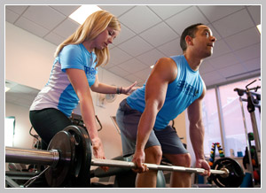 Personal Trainer Heidi Berio spots her PT client as he performs a weight lifting exercise.